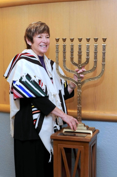 Rabbi Barbara Aiello stands with synagogue menorah as she welcomes Italy's first modern rabbinic intern to the Calabrian synagogue, Ner Tamid del Sud in Serrastretta, Italy.