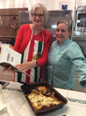 Kathy Nano Bolanowski with Chef Jen holding Italian cookbook.
